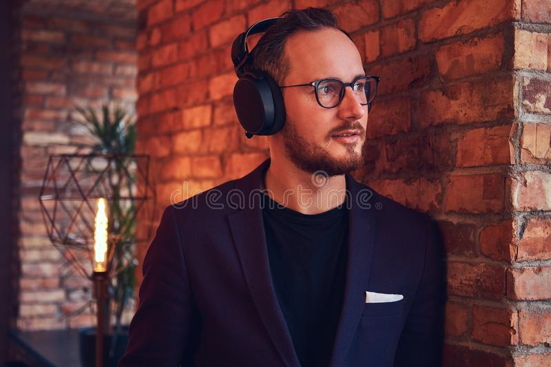 Close-up portrait of a handsome bearded male wearing stylish suit listening music in headphones against a brick wall. royalty free stock photo