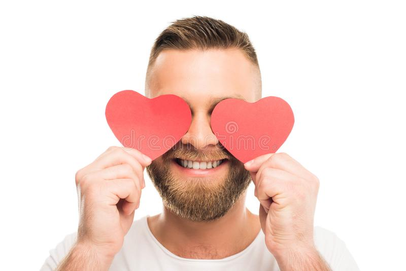 Close-up portrait of handsome bearded man closing eyes by red paper hearts,. Isolated on white royalty free illustration