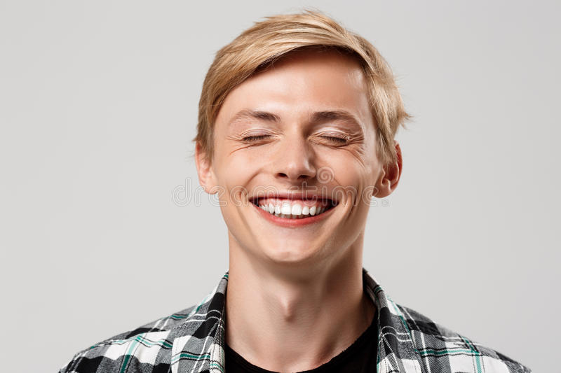 Close up portrait of handsome blond young man wearing casual plaid shirt smiling with eyes closed isolated on grey royalty free stock image