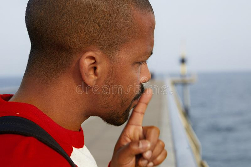 Close up portrait of handsome cheerful silent american african man making hush gesture at the beach. stock photo