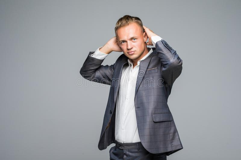 Close up portrait of handsome confident masculine man in jacket touching his hair on gray stock images