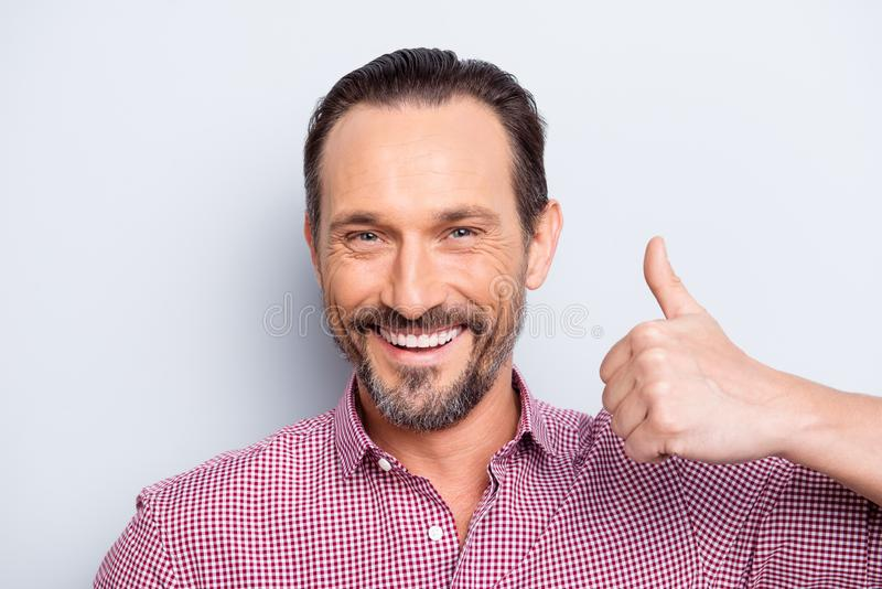 Close up portrait of handsome good-wearing attractive man make b. Eaming toothy smile stand isolated on light gray background show thumb up look at camera royalty free stock photography