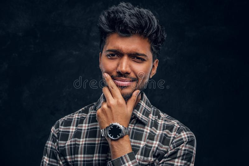 Close-up portrait of a handsome Indian man wearing a plaid shirt posing with hand on chin. Studio photo against a dark textured wall stock image