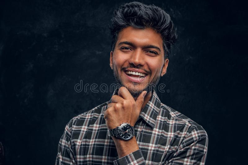 Close-up portrait of a handsome Indian man wearing a plaid shirt posing with hand on chin, smiling and looking at a. Camera. Studio photo against a dark royalty free stock photo