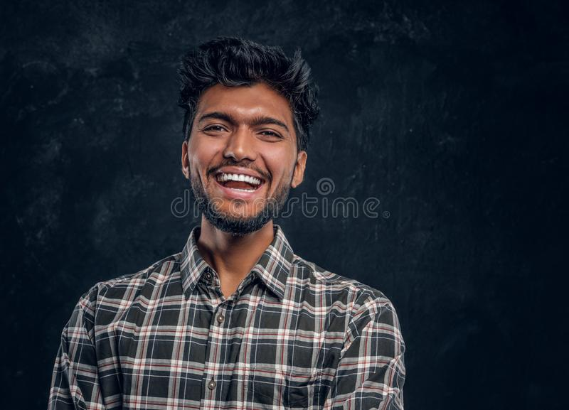 Close-up portrait of a handsome Indian man wearing a plaid shirt, smiling and looking at a camera. Cheerful young Indian man wearing a plaid shirt, laughing and royalty free stock photo