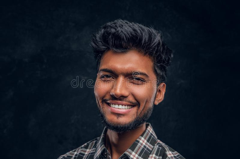 Close-up portrait of a handsome Indian man wearing a plaid shirt, smiling and looking at a camera. Studio photo against a dark textured wall stock photos