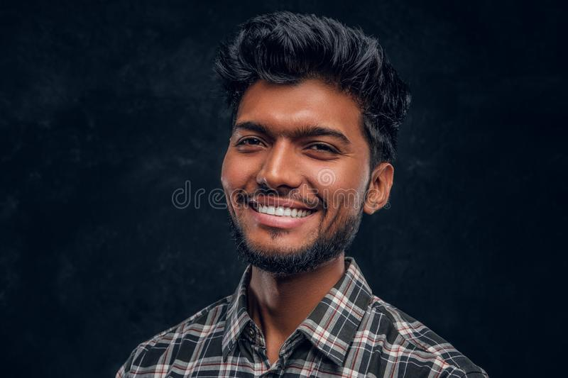 Close-up portrait of a handsome Indian man wearing a plaid shirt, smiling and looking at a camera. Studio photo against a dark textured wall stock image