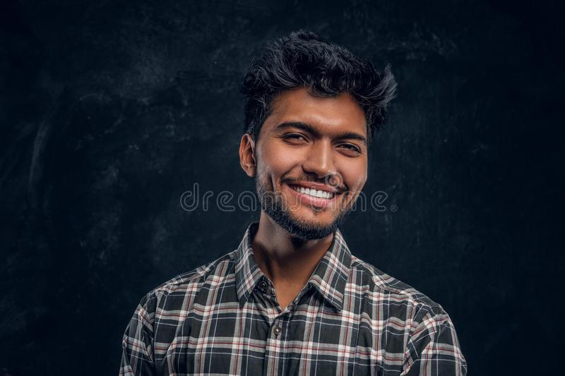Close-up portrait of a handsome Indian man wearing a plaid shirt, smiling and looking at a camera. Studio photo against a dark textured wall stock photo