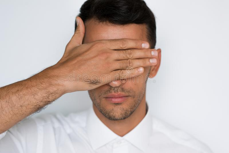 Close-up portrait of handsome man cover eyes with hand isolated on gray background. Attractive businessman blindfolded protection. royalty free stock photography