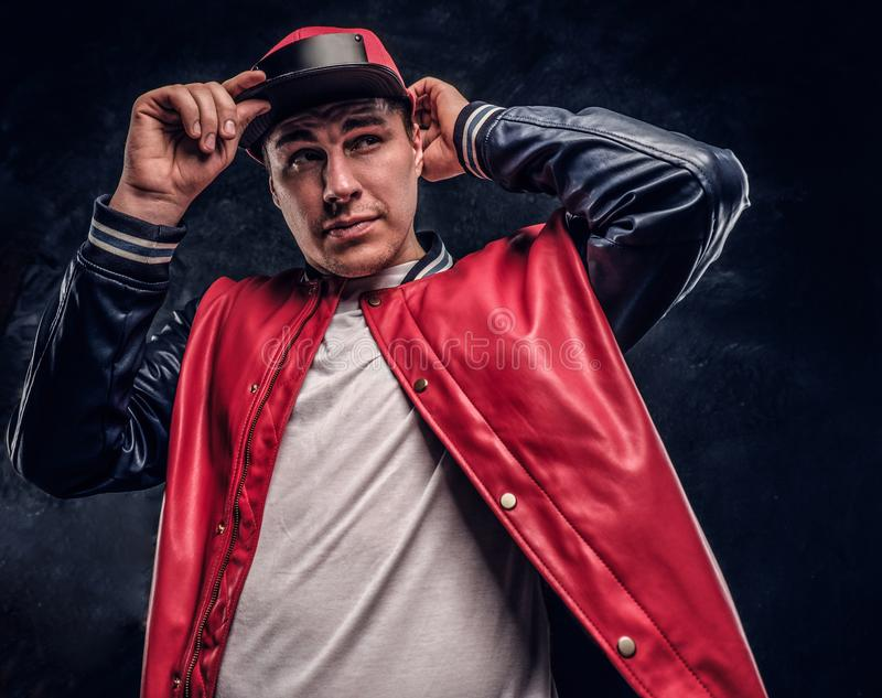 Close-up portrait of a handsome man dressed in a hip-hop style. Studio photo against a dark wall royalty free stock image