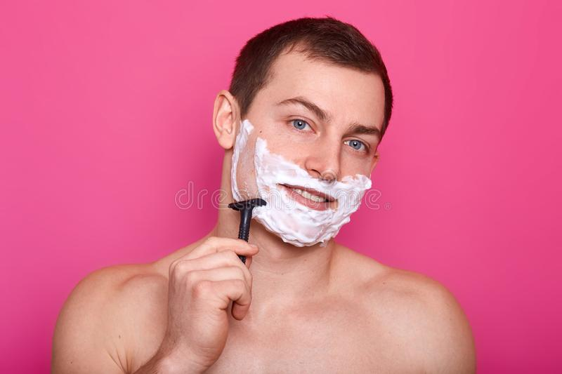 Close up portrait of handsome man with foam on face, shaving with razor in bathroom, looking smiling at camera, posing with bared. Shoulders  on pink background royalty free stock images