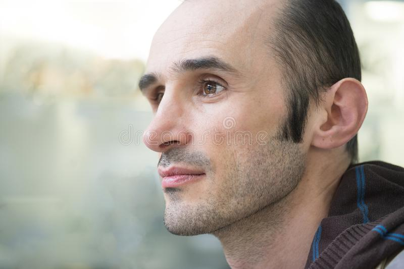 Close up portrait of a handsome man looking away on  blurred background royalty free stock photo