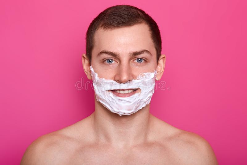 Close up portrait of handsome man with shaving foam on his face isolated over pink background. Man shaves his beard in bathroom. stock photos