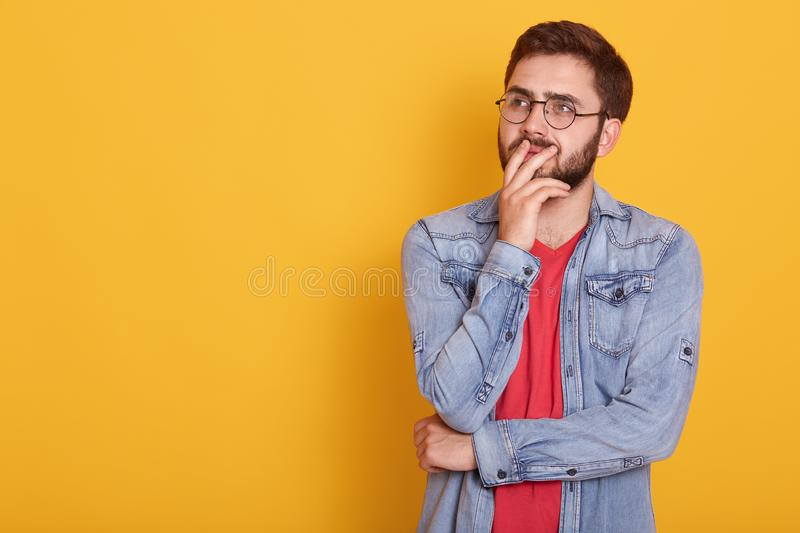 Close up portrait of handsome man wearing stylish denim jacket, red shirt and glasses, looks aside with thoughtful facial royalty free stock photography