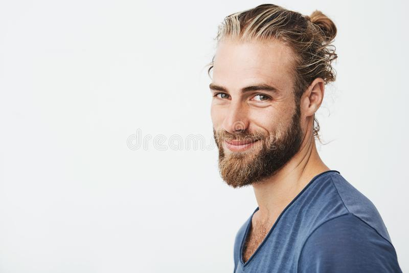 Close up portrait of handsome manly guy with beard posing in three quarters, looking in camera and happily smiling stock photos