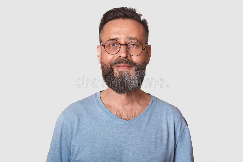 Close up portrait of handsome middle aged bearded Caucasian man with smile, male wearing gray casual t shirt, posing isolated over stock photography