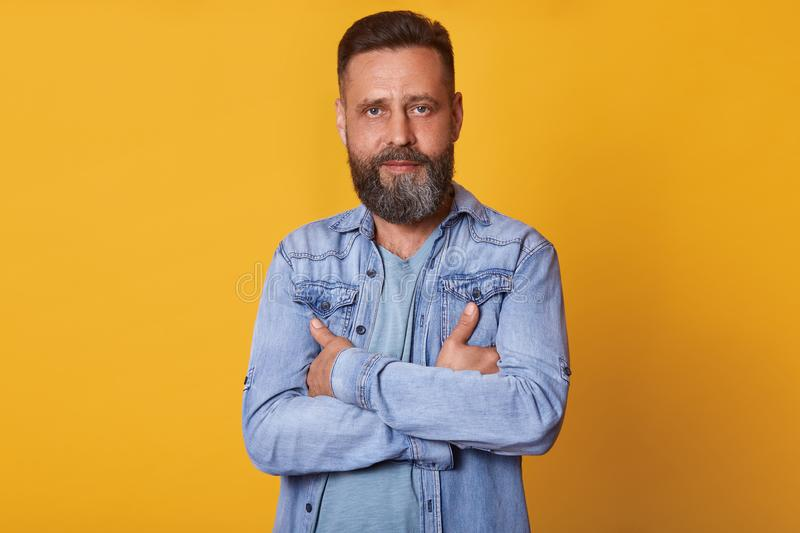 Close up portrait of handsome middle aged Caucasian man with beard, posing isolated on yellow background, wears denim jacket and royalty free stock photography