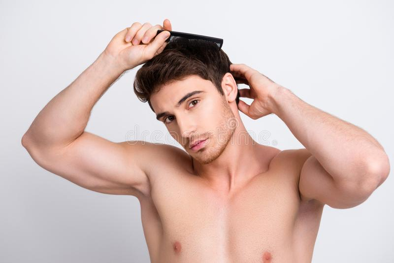 Close up portrait of handsome muscular naked nude strong brunette man with bristle stubble combing his ideal perfect brown hair u. Sing black flat comb isolated stock image
