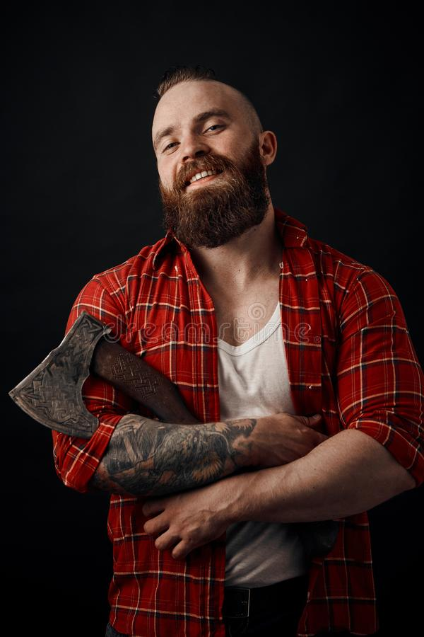 Smiling bearded man holding axe looking at camera on black background stock image