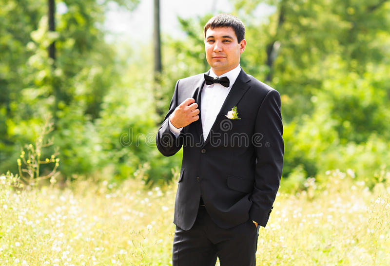 Close up portrait of handsome stylish groom in black classic suit outdoors stock photography