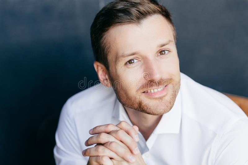 Close up portrait of handsome unshaven male with positive smile, keeps hands together, feels successful as works in business spher stock images