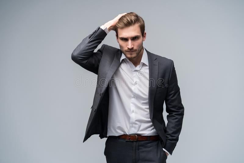 Close up portrait of a handsome young businessman dressed in suit isolated over gray background, looking away. stock photo