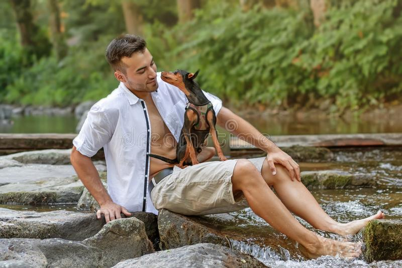 portrait of handsome young man with dog, outdoor stock photography