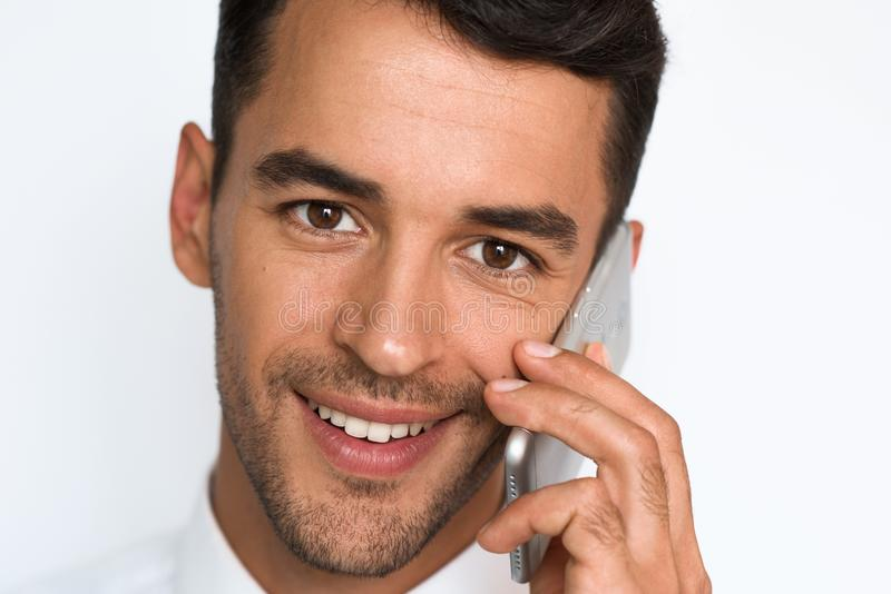 Close up portrait of handsome young smile man in white shirt using mobile phone, looking at the camera with happy expression. royalty free stock photo
