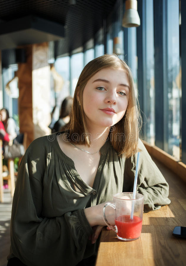 Close up portrait of happy beautiful teen student girl with a glass mug straw fruit tea at street cafe sitting near big window royalty free stock photos