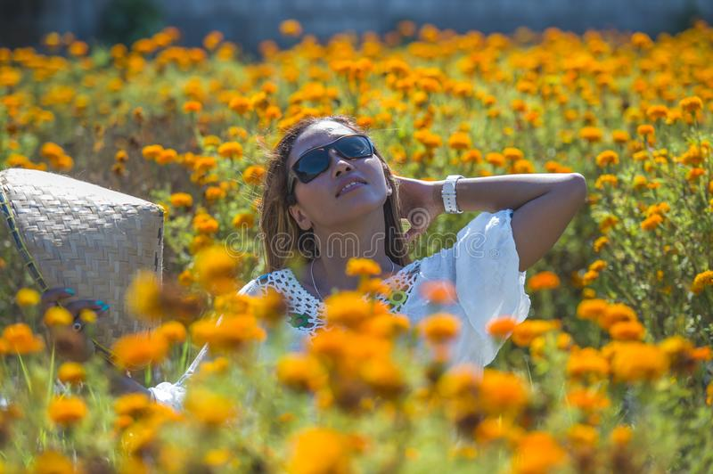 Close up portrait happy and beautiful young Asian woman relaxing enjoying the fresh beauty of gorgeous orange marigold flowers fie royalty free stock image