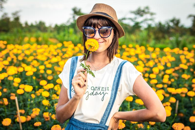 Close up portrait of happy and beautiful young woman relaxing enjoying the fresh beauty of gorgeous orange marigold royalty free stock image