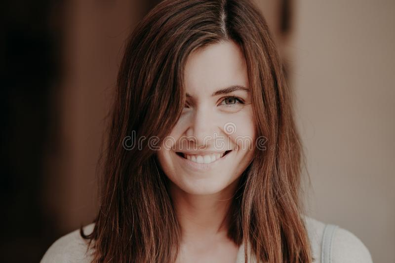 Close up portrait of happy brunette woman with toothy smile, looks happily at camera, healthy skin, natural beauty, poses indoor. royalty free stock photography