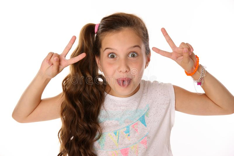Close-up portrait of happy child girl makes comical face and shows her tongue royalty free stock photos
