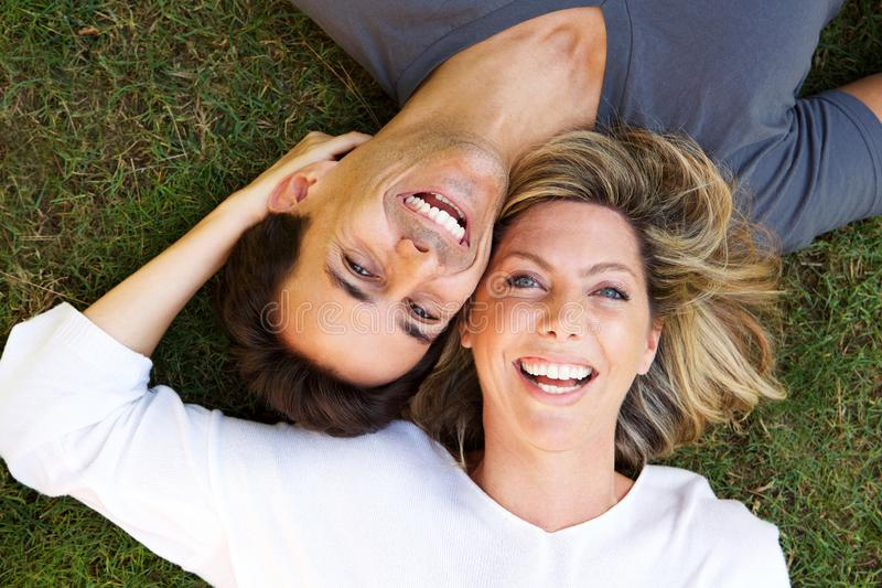 Close up happy couple lying on grass together laughing. Close up portrait of happy couple lying on grass together laughing stock photo