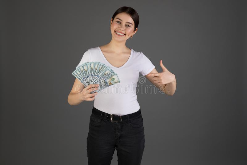 Close up portrait of happy eurupean woman holding money  on grey background stock photography