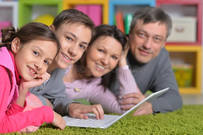 Close up portrait of happy family lying on floor in front of laptop stock image