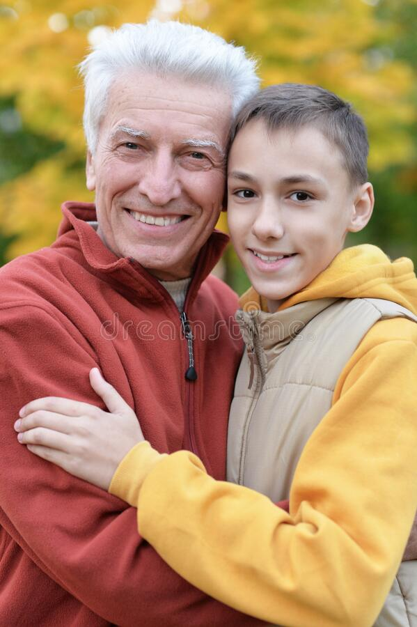 Portrait of happy grandfather and grandson in park royalty free stock images
