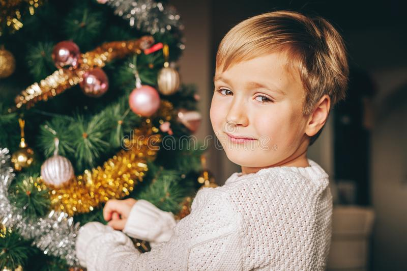 Close up portrait of happy little boy playing next to christmas tree stock photo