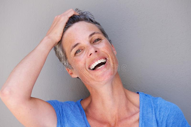 Close up happy older woman laughing with hand in hair. Close up portrait of happy older woman laughing with hand in hair stock photography