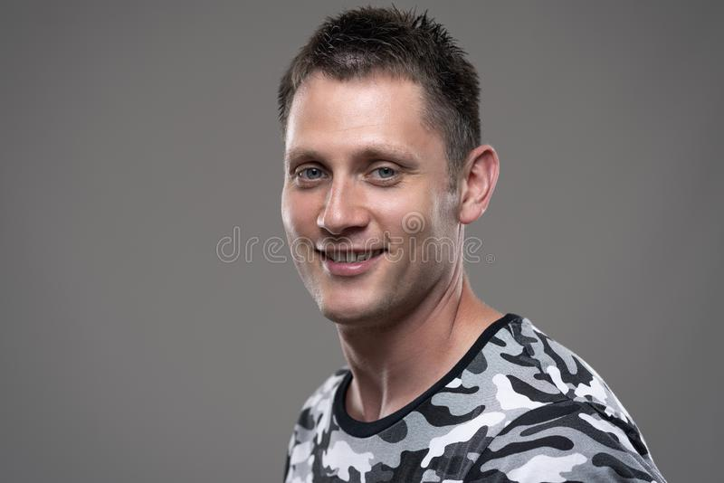 Close up portrait of happy relaxed young adult man in army shirt smiling at camera. On gray background stock images