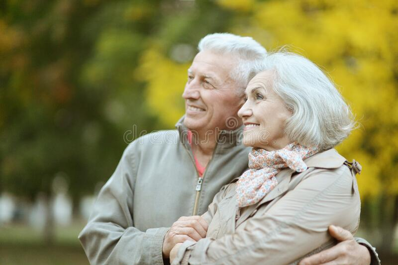 Happy senior couple posing in the park royalty free stock photography