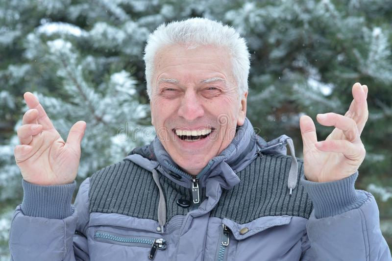Close up portrait of happy senior man standing outdoors in winter royalty free stock photo