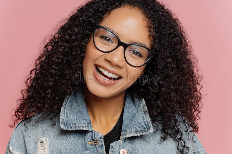 Close up portrait of happy smiling woman with dark curly Afro hairstyle, tilts head, wears optical glasses and denim jacket, royalty free stock photos