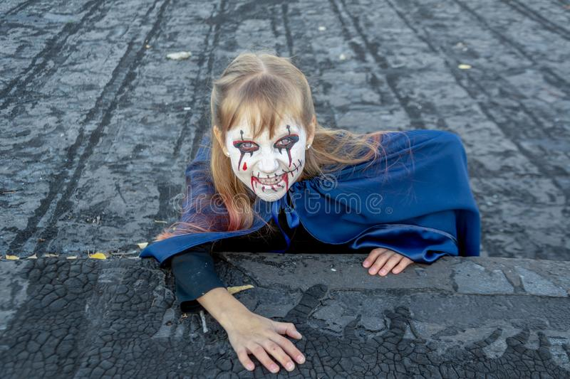 Close-up portrait of a happy and smiling a zombie girl on the roof of the house. The monster comes out of the dark. Red eyes. stock photo