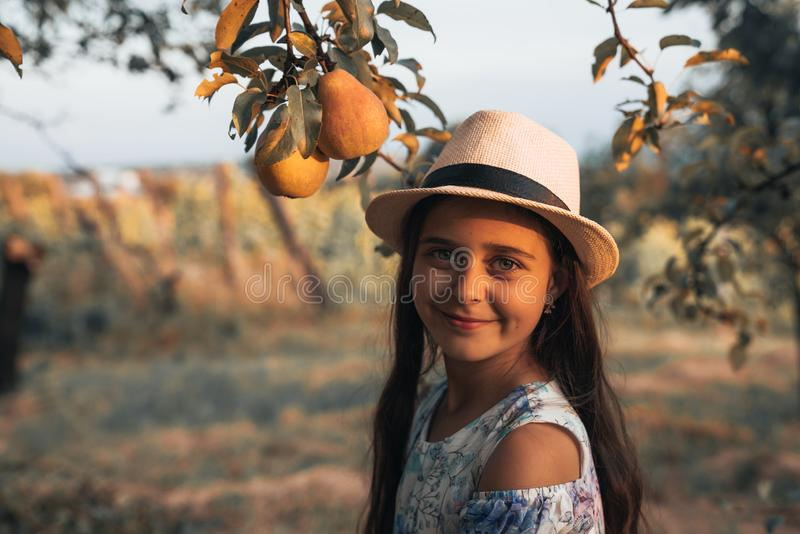 Close up portrait of happy teen girl with healthy skin in white hat and dress standing in the garden, two pears are stock images