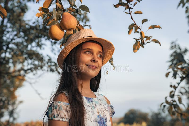 Close up portrait of happy teen girl with healthy skin in white hat and dress standing in the garden, two pears are stock photography