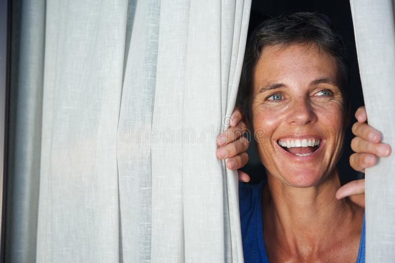 Close up happy woman opening curtain and looking through window. Close up portrait of happy woman opening curtain and looking through window royalty free stock images