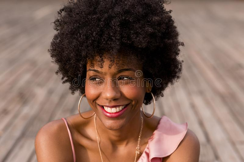 close up portrait of a Happy young beautiful afro american woman sitting on wood floor and smiling. Spring or summer season. royalty free stock images