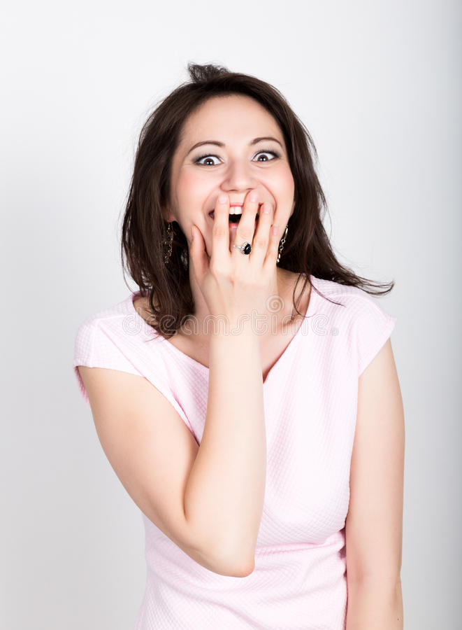 Close up portrait happy young beautiful brunette woman closes mouth by hand. Shocked surprised stunned. Positive human stock photos