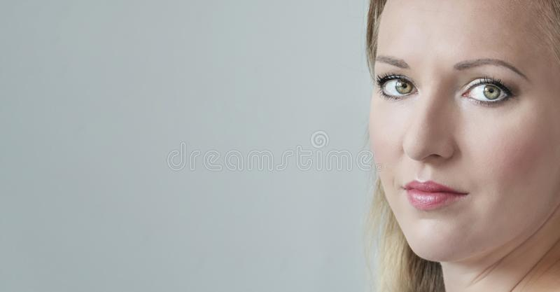 Close-up portrait of happy young beautiful woman face looking at camera. Blonde woman with green eyes stock image